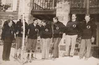 A photograph showing a group of men standing together in skis.