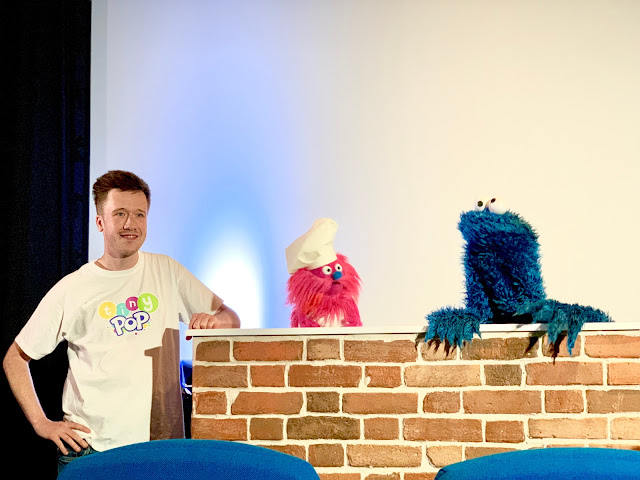 A host standing next to a brick wall with Gonger and Cookie Monster behind it
