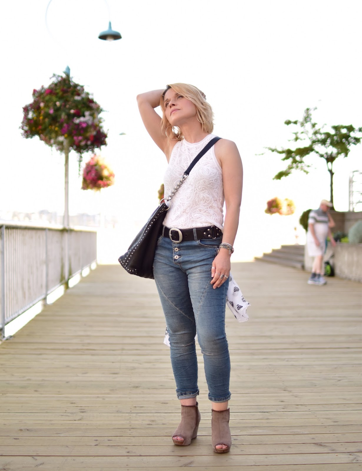 Monika Faulkner styles skinny jeans with a lacy tank, open-toe wedge booties, and MK bag
