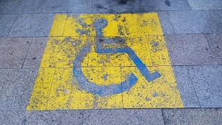 Señal pintada en el suelo de sitio reservado para personas con discapacidad.
