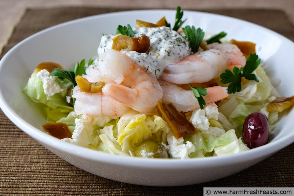 photo of a bowl of Mediterranean shrimp salad atop a bed of lettuce with spiced Greek yogurt, olives, and feta cheese