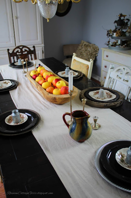 Black table set with a beige table runner. A wooden bread bowl filled with red and yellow apples. Wooden chargers with black plates silver candle sticks and brown pitcher in gray room apple tablescape - Fall Decor, Autumn Decorating, Table Decor, Cottage, Country, Natural Decor,