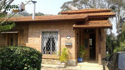 Casa com base de pedra, tipo revestimento de pedra com chapas de pedra moledo em casa com parede de tijolo a vista em condomínio em Atibaia-SP.