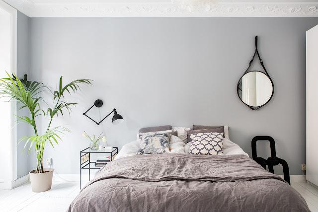 szara ściana w sypialni, okrągłe lustro na pasku
