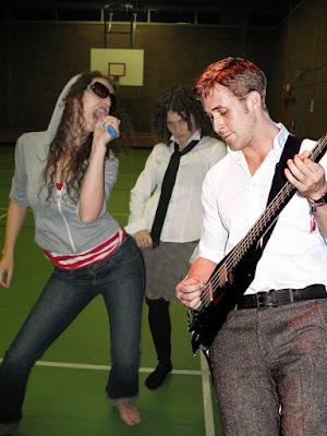 Ryan Gosling didn't quite understand that you don't bring a guitar to air band rehearsal - he looks cute though, doesn't he?
