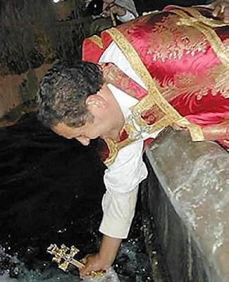 O sacerdote imerge a Cruz na fonte e abençoa as águas
