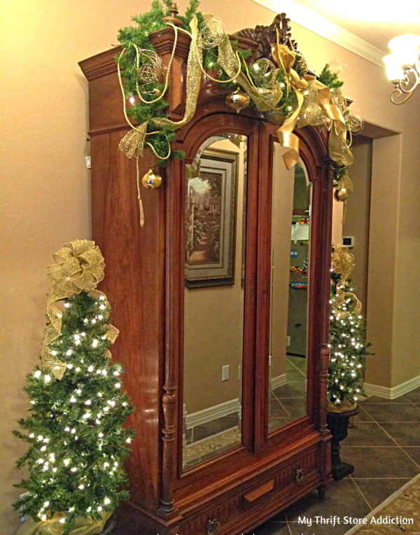 Traditional greenery and gold adorned armoire