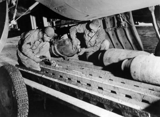 Los hombres de tierra preparando las bombas de los aviones