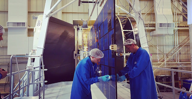 Engineers examine one of Orion's solar array wing after a test. Credit: NASA
