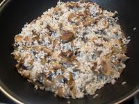 Arroz mezclado y rehogando con la cebolla, las setas