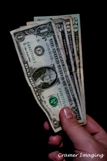 Cramer Imaging's professional quality photograph of a hand holding a one, five, ten, and twenty dollar bill in Pocatello, Bannock, Idaho