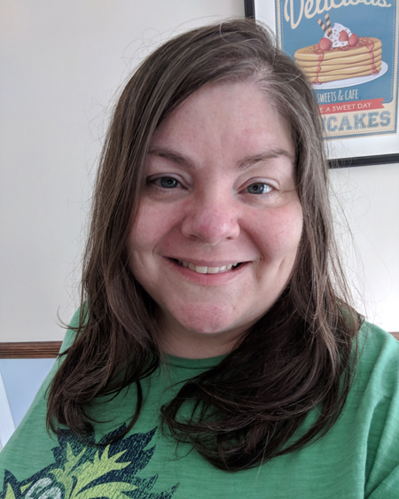 image of me from the shoulders up in a green t-shirt and wearing contacts, with my hair down, smiling widely