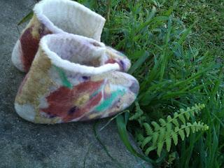 Pantufa feltrada com lã na cor crua, flore marrom e detalhes coloridos e bordada com fio de algodão.