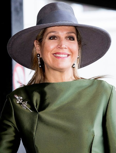 Queen Maxima wore a green dress by Natan and carried Chanel bag. . Queen wore Natan shoes. Natan is a fashion house founded by Edouard Vermeulen