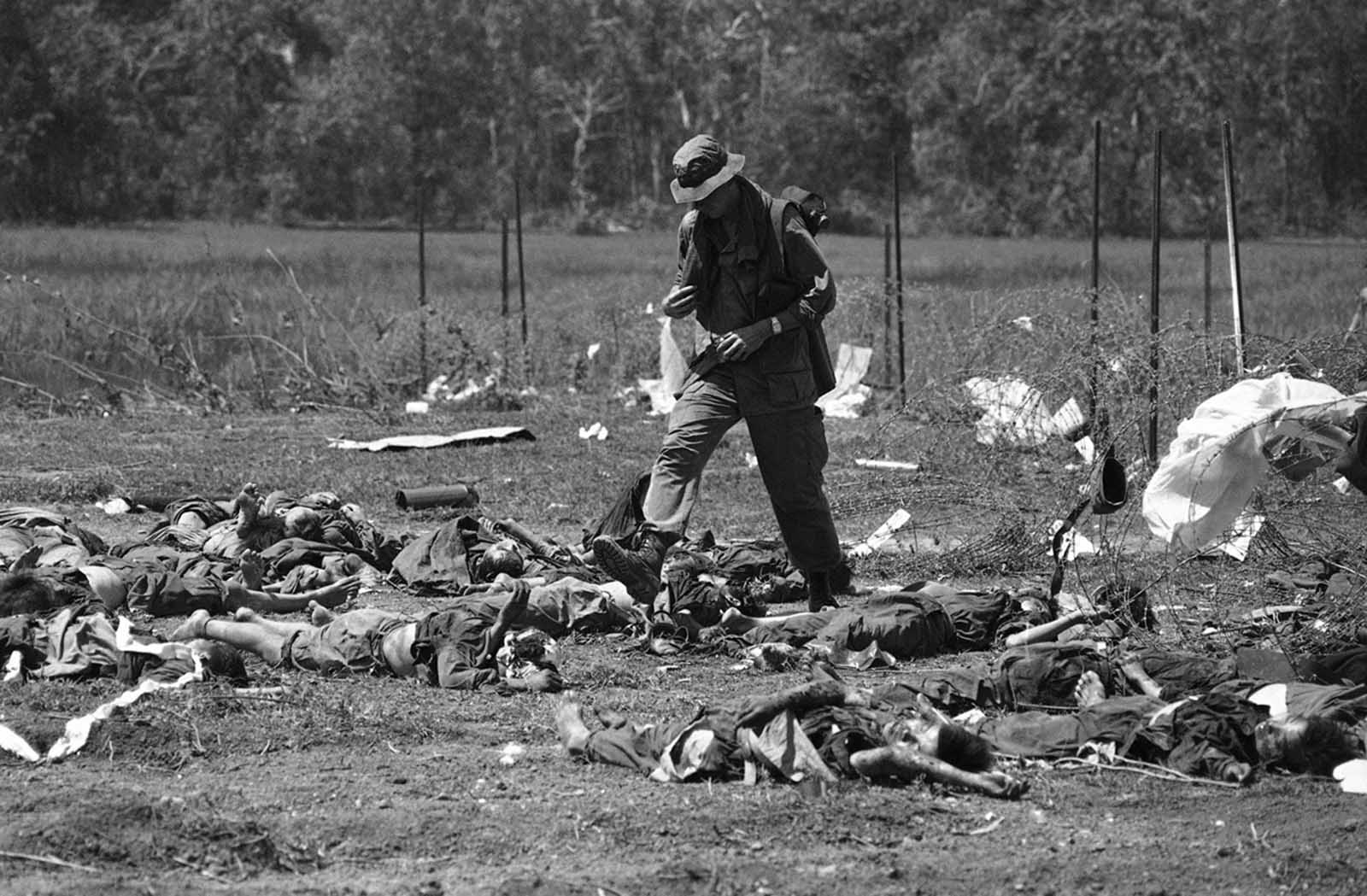 A GI of the U.S. 199th light infantry brigade walks through bodies laid out just outside the barbed wire perimeter of U.S. firebase crown in Cambodia on May 14, 1970. Fifty North Vietnamese were killed and only four Americans wounded when the North Vietnamese, presumably thinking the firebase already abandoned, walked into an ambush by the American defenders.