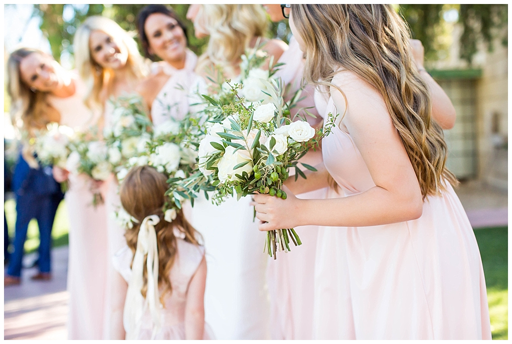 white floral bouquet with greenery and bridesmaids in blush dresses