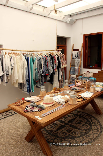 A table in a shop decorated with clothes to buy in front of hanging rails with dresses.