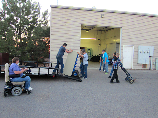Young people move equipment off a trailer while a woman in a wheelchair looks on.