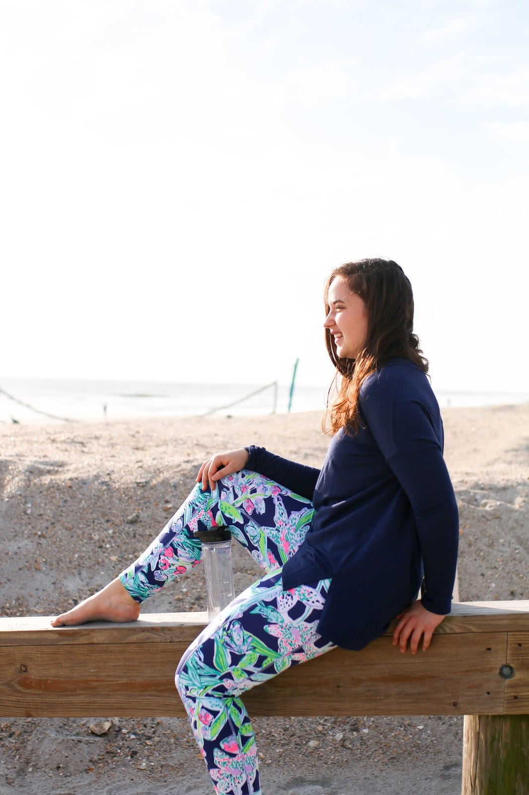 Brunette girl sitting at the beach in lilly pulitzer luxletic leggings and tee