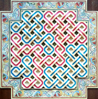 The board at the end of a game. The board is square, with the corners cut out so it forms a sort of cross shape. Along the edge of the board is complex celtic knotwork in an elaborate zoomorphic theme with birds entwined. The play area itself is filled with plastic pieces; these are rings in both blue and red which are joined to the pieces next to them with 'bridges' that combine the rings into a celtic knotwork pattern.
