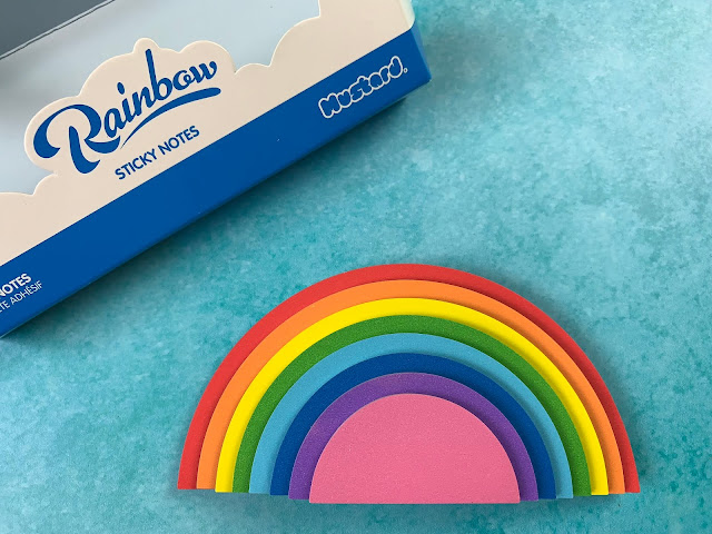 A stack of semi circle sticky notes in rainbow colours creating a 3d rainbow shape