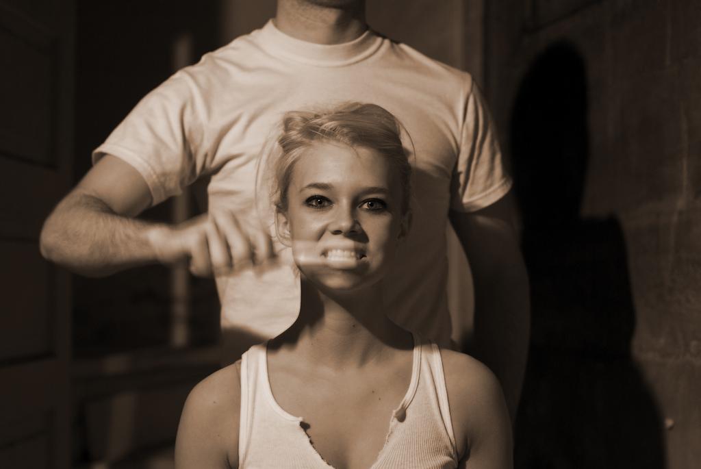 Man brushing girl's teeth