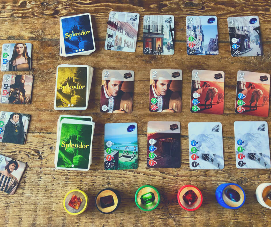 Splendor board game cards and tokens set up on a wooden table.
