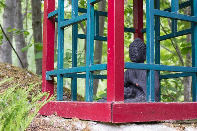 Mietiskelevän buddhan patsas kiinalaisessa puutarhassa.