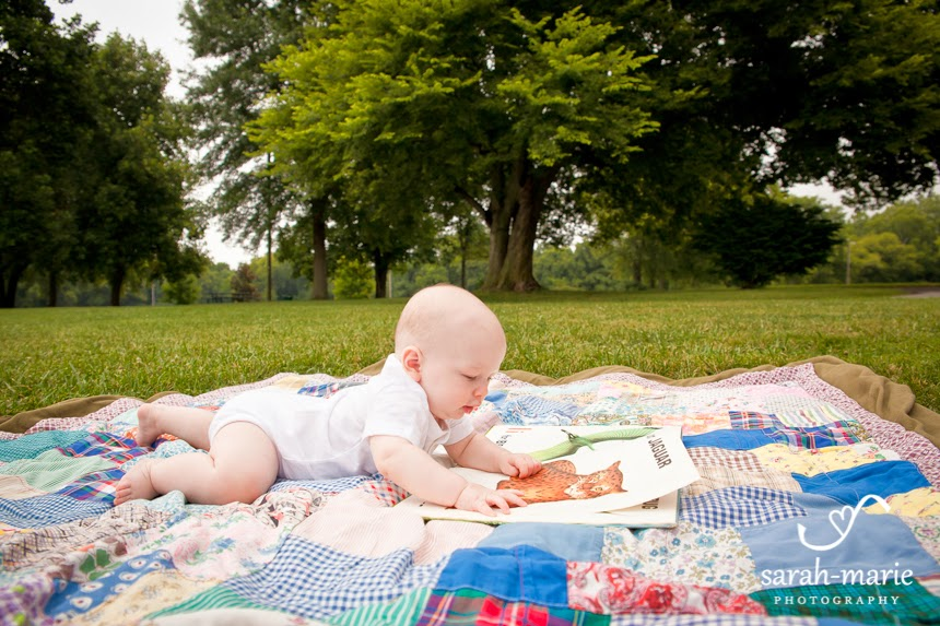 baby reading on quilt