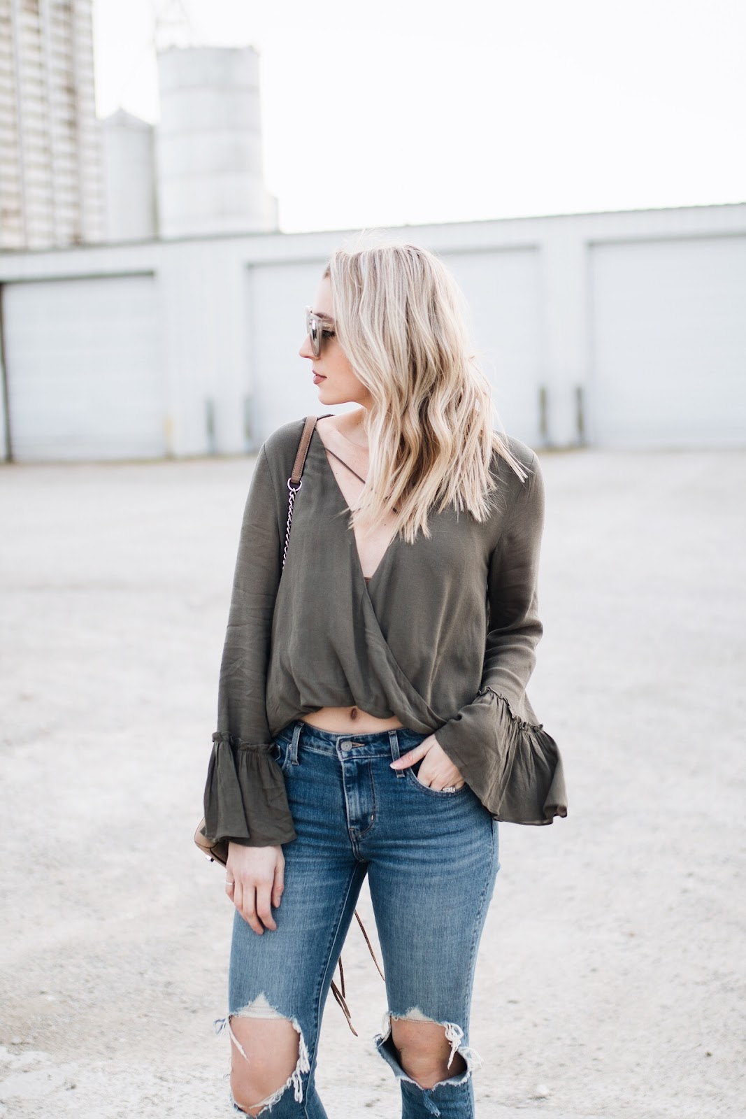 olive top, ripped jeans