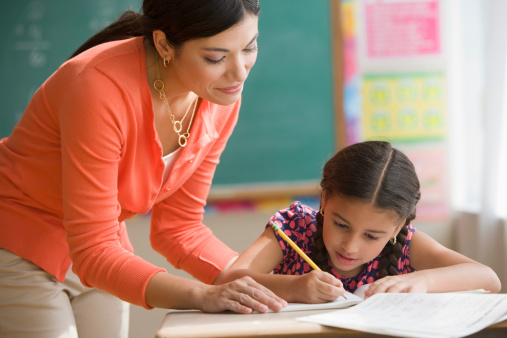 professora ajudando aluna sala de aula
