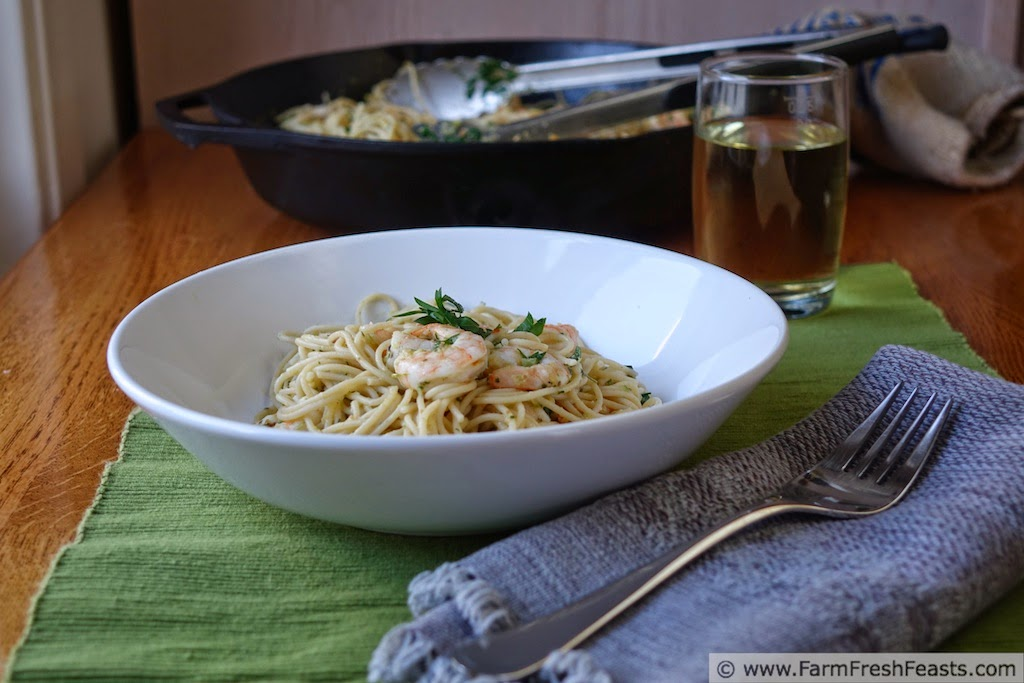 image of a plate of shrimp scampi over thin spaghetti noodles seasoned with garlic scape pesto