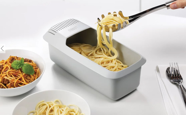 image of the pasta cooker sitting on a dining table with cooked spaghetti being spooned out of it