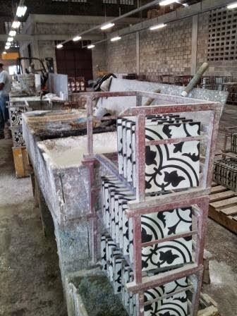 Handmade cement tiles are dried and set to age on racks, allowing them to harden prior to shipping.