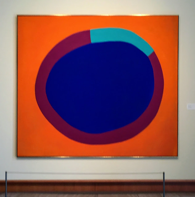Ultramarine blue circle surrounded by an arc of red and light blue sits on an orange background