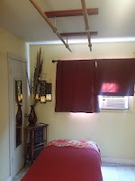 A relaxing massage treatment room with Ashiatsu bars, candles, and a/c