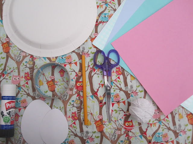 Craft supplies, including card, paper plate, tape, glue, egg template, pencil, scissors, string