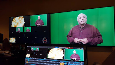 The CMAC control room monitors show the studio camera views as William Elliott, producer and host talks about Guy Fawkes and the gunpowder plot in the green screen studio while recording 'Remember, Remember'