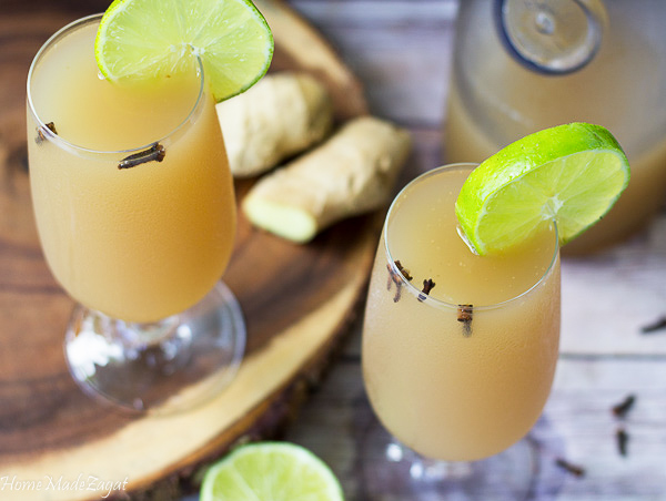 Close up of two glasses of ginger beer with cloves and limes