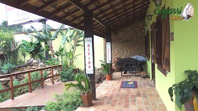 Piso de tijolo de demolição no terraço da cabana com os pilares de madeira, o piso de madeira no deck da cabana com execução do paisagismo com pedras.