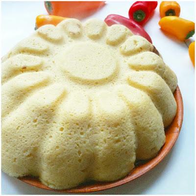 Vista lateral de un pastel de coliflor desprendiendo calor y con mini pimientos de acompañamiento