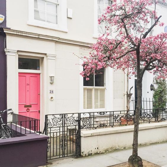 Bright pink door on painted brick and decorative wrought iron fence beautiful home exterior seen on Hello Lovely Studio