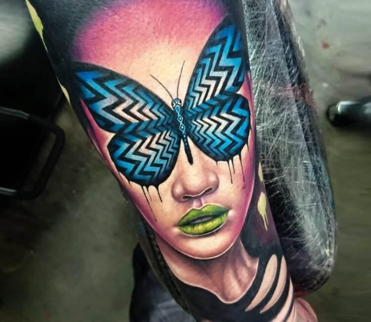 Tatuaje de un rostro a color con una mariposa tapando su mirada