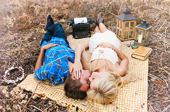 An engagement photo of a couple laying on the ground surrounded by a lantern, books, and a vintage typewriter