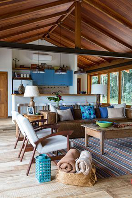 Ambiente rústico com tapete listrado colorido nos mesmos tons da decoração