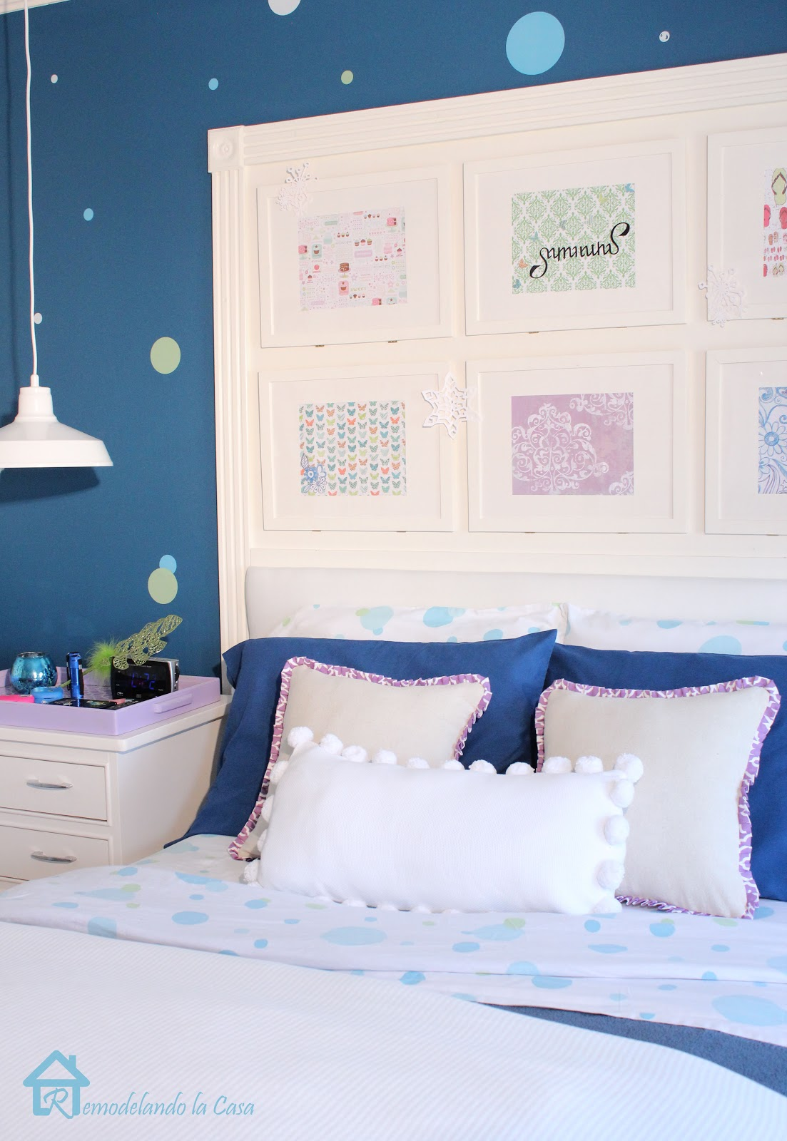 pictures frames put together to create a bed's headboard in girl room
