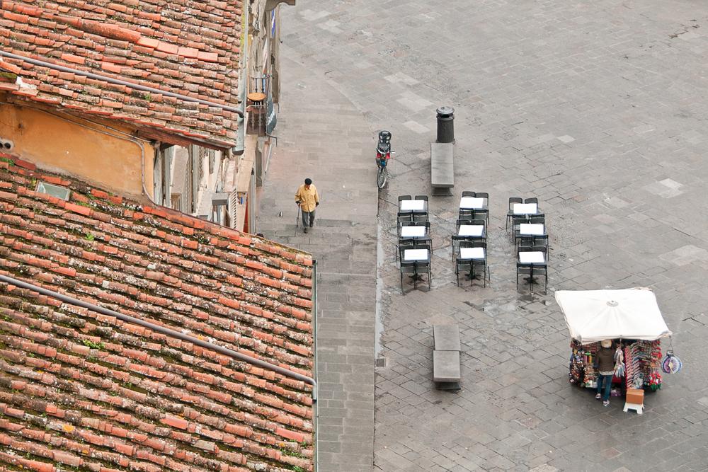 Un homme se balade dans la rue à Florence en Italie. Il passe près d'une terrasse. La photo à été prise du haut du campanile de Florence
