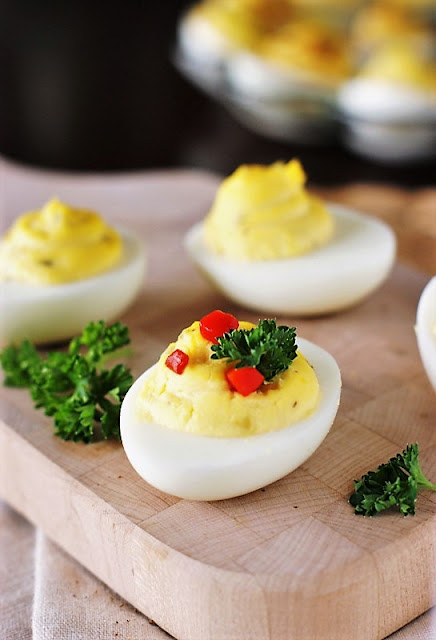 Deviled Eggs Garnished with Parsley and Pimento Image