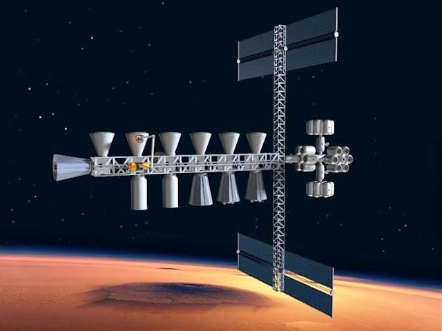 In this artist's conception, a fleet of spaceships has entered Martian orbit, and robots have assembled the docking truss and the rest of a way station and crew quarters in Martian orbit. Other vehicles, including fuel depots, have hooked up to the truss. Cargo is being transferred from transit vehicles to a cargo ferry for the trip down to the Martian surface. Credit: John K. Strickland