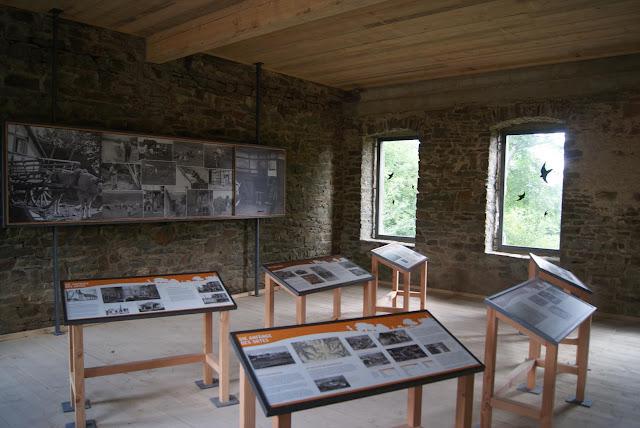 In einem Raum sind mehrere Infotafeln aufgestellt. An der Wand hängt ein großes Bild